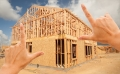 Photo of fingers framing a house under construction